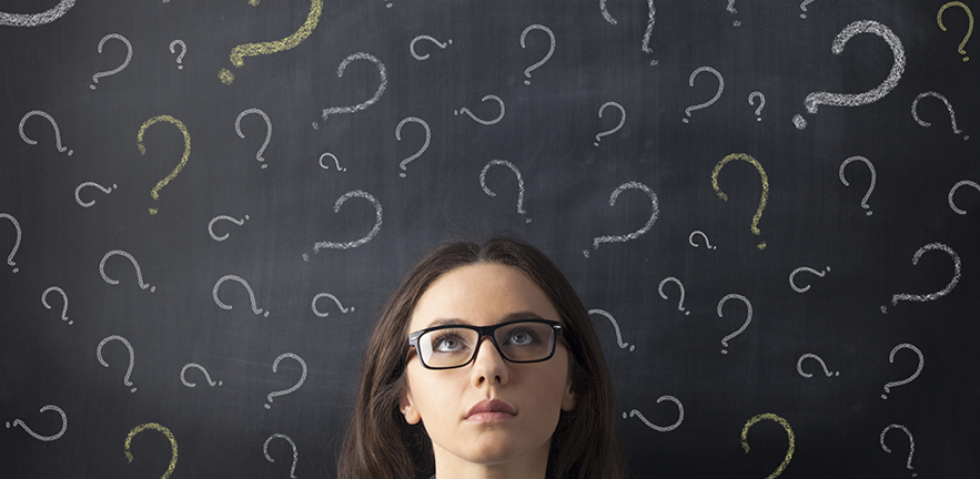 Businesswoman's head is visible surrounded by question marks drawn on a blackboard behind her. The woman is facing the viewer, and her eyes look up.